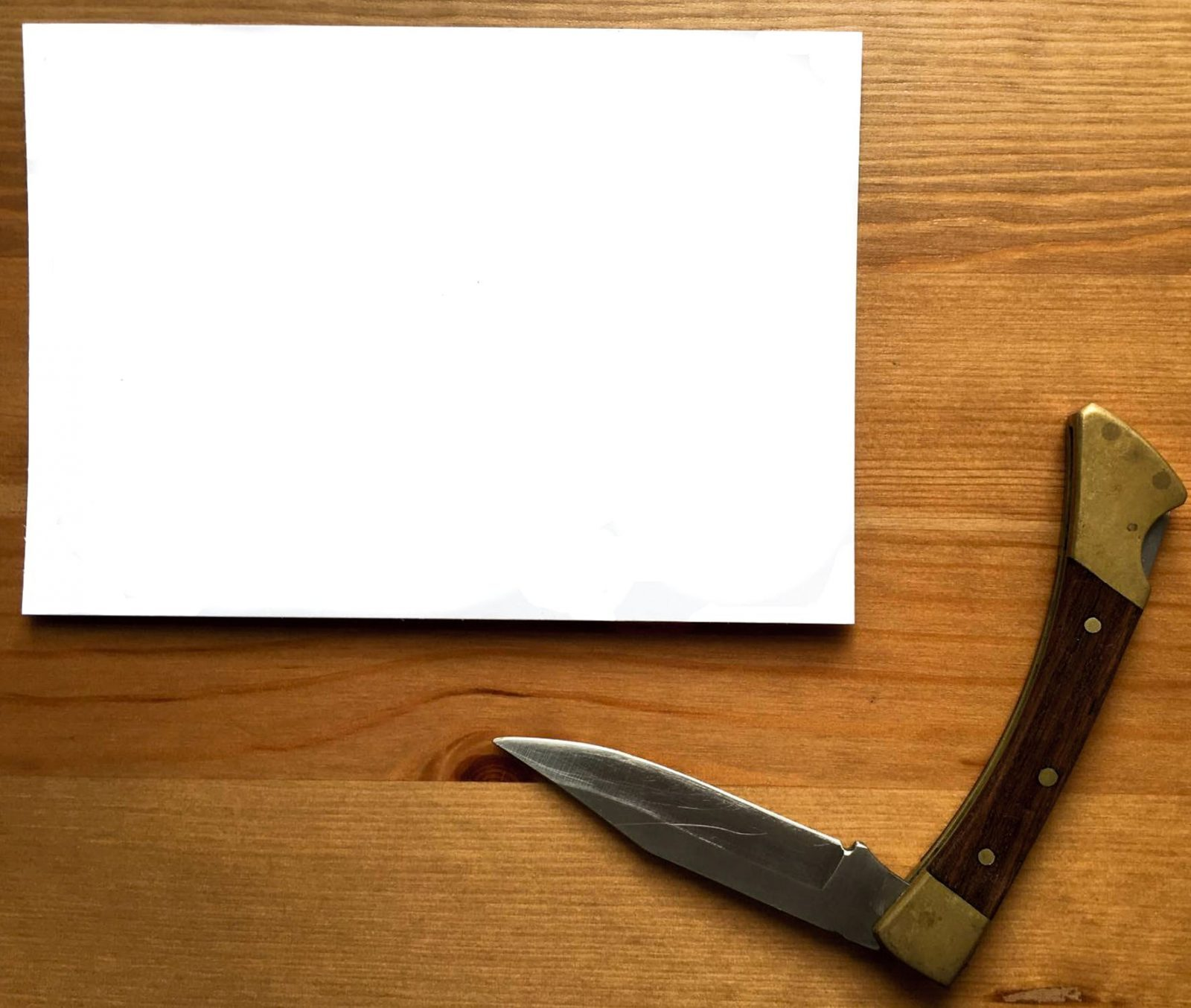 custom folding knife on wooden desktop next to paper