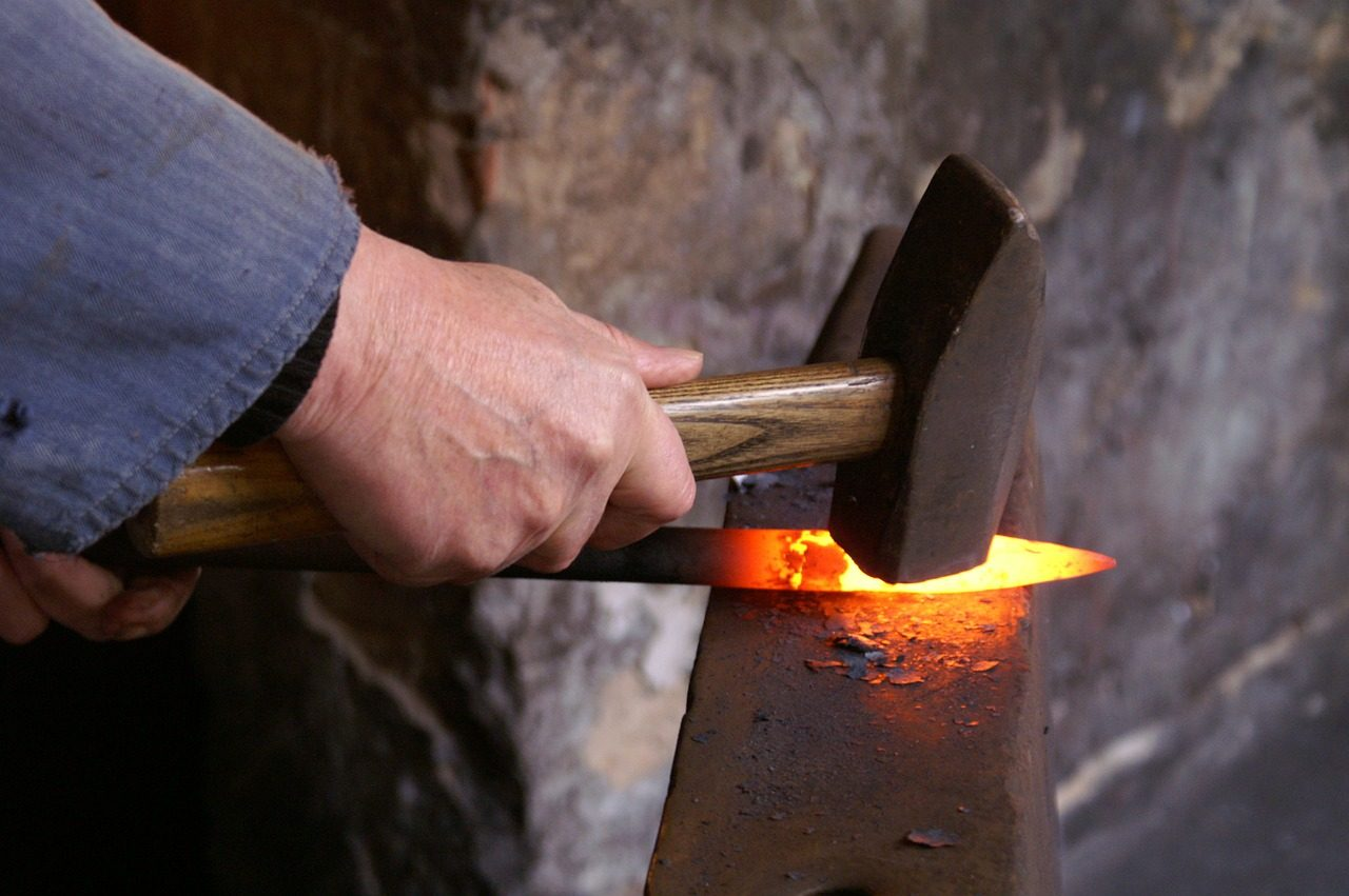 man hammering knife at forge